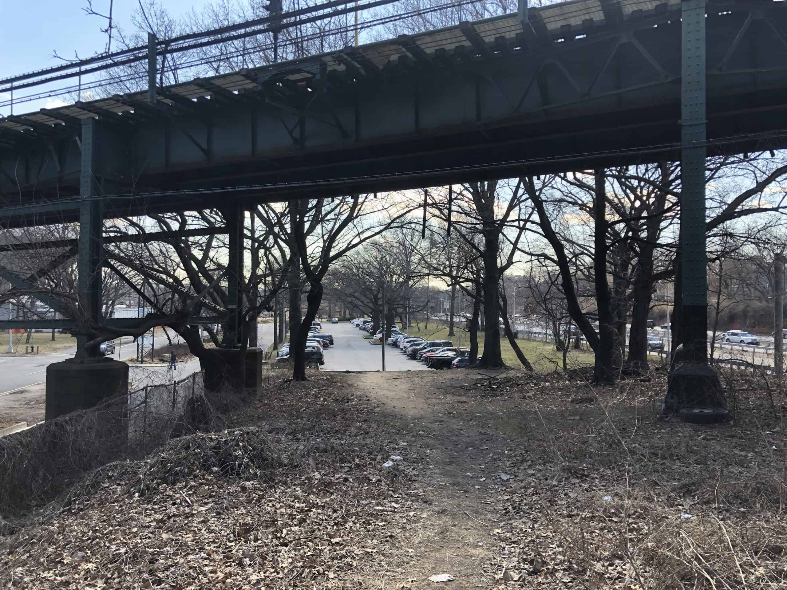 train overpass over a road and forest pedestrian trail