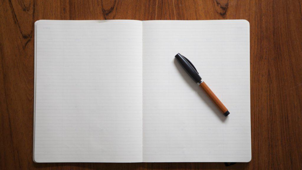pen on an open and empty notebook