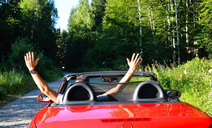 Man driving a red convertible with hands in the air, wife bent down in passengers seat