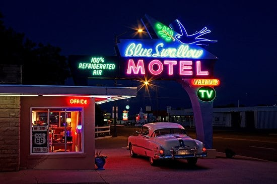 """car pulling into classic 70's motel drive in. With neon signs that say """"motel"""""""