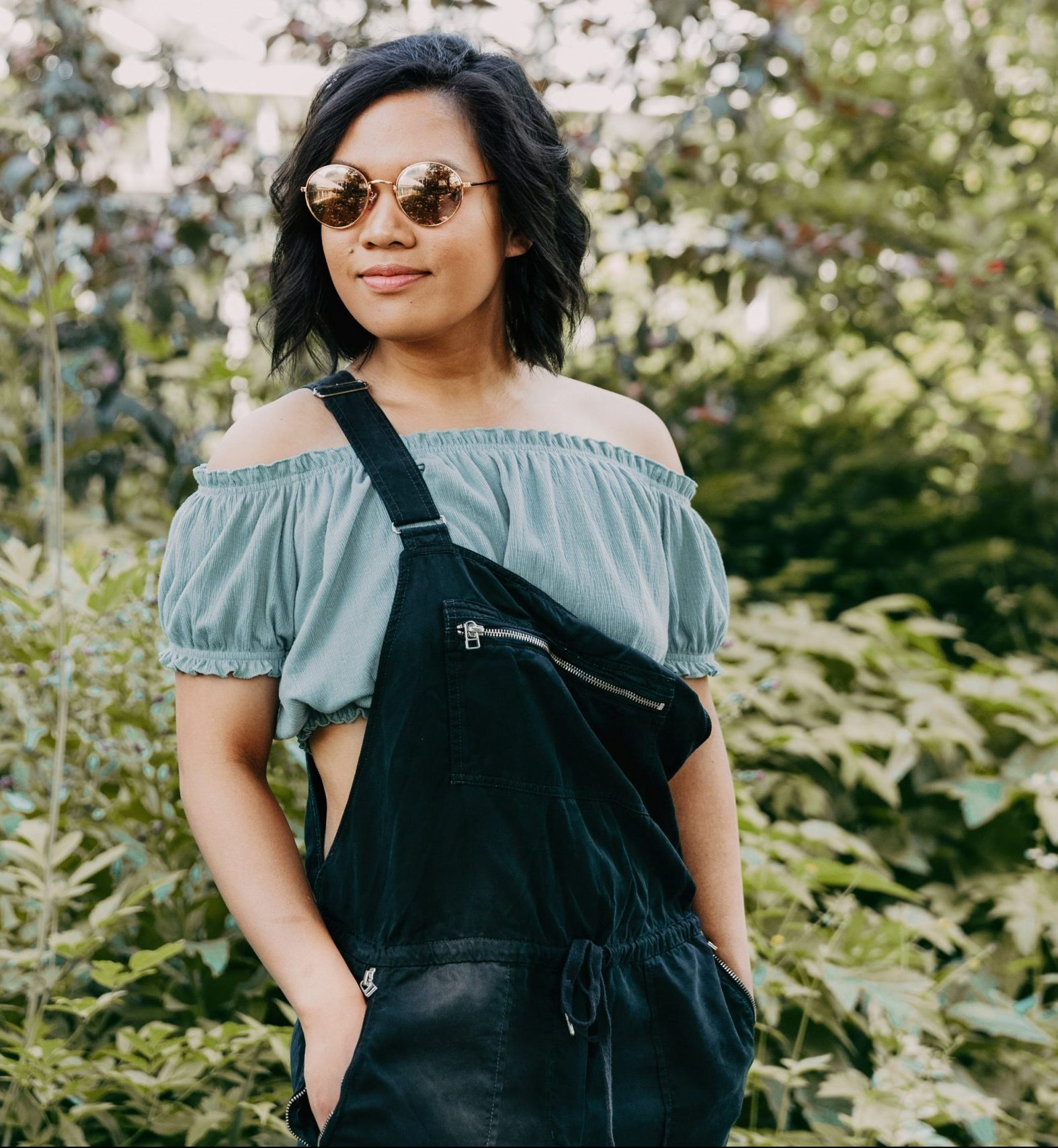 stylish confident woman wearing sunglasses and overalls in front of a field