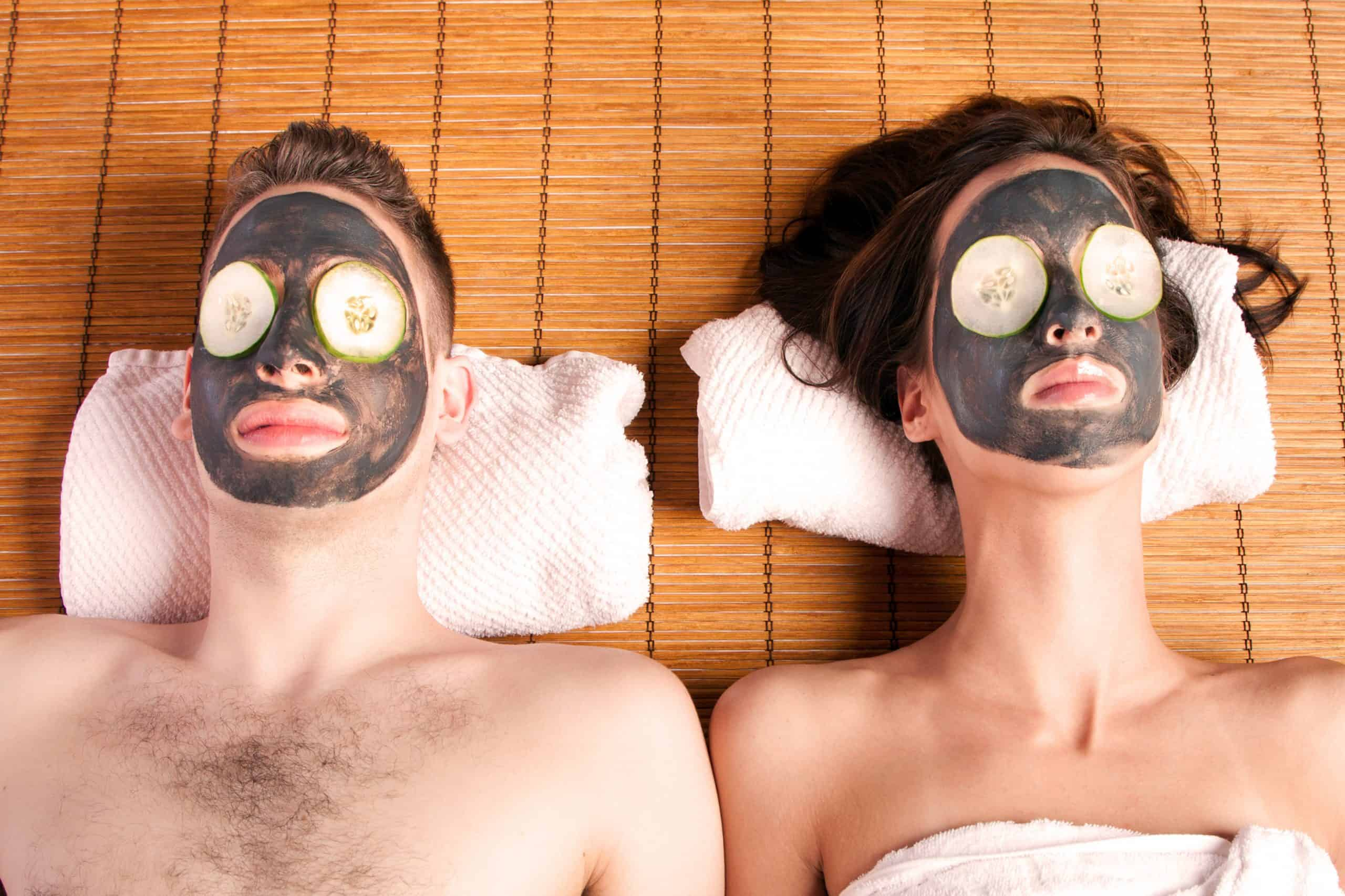 Couples holiday retreat at spa getting facial mask with cucumber skincare relaxing beauty treatment on bamboo.