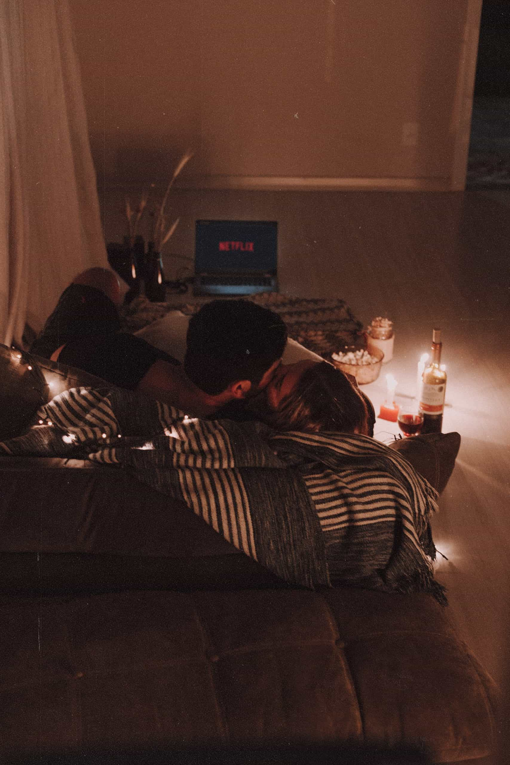 Couple having some netflix and chill, cuddling on the sofa with popcorn, candles and a bottle of wine