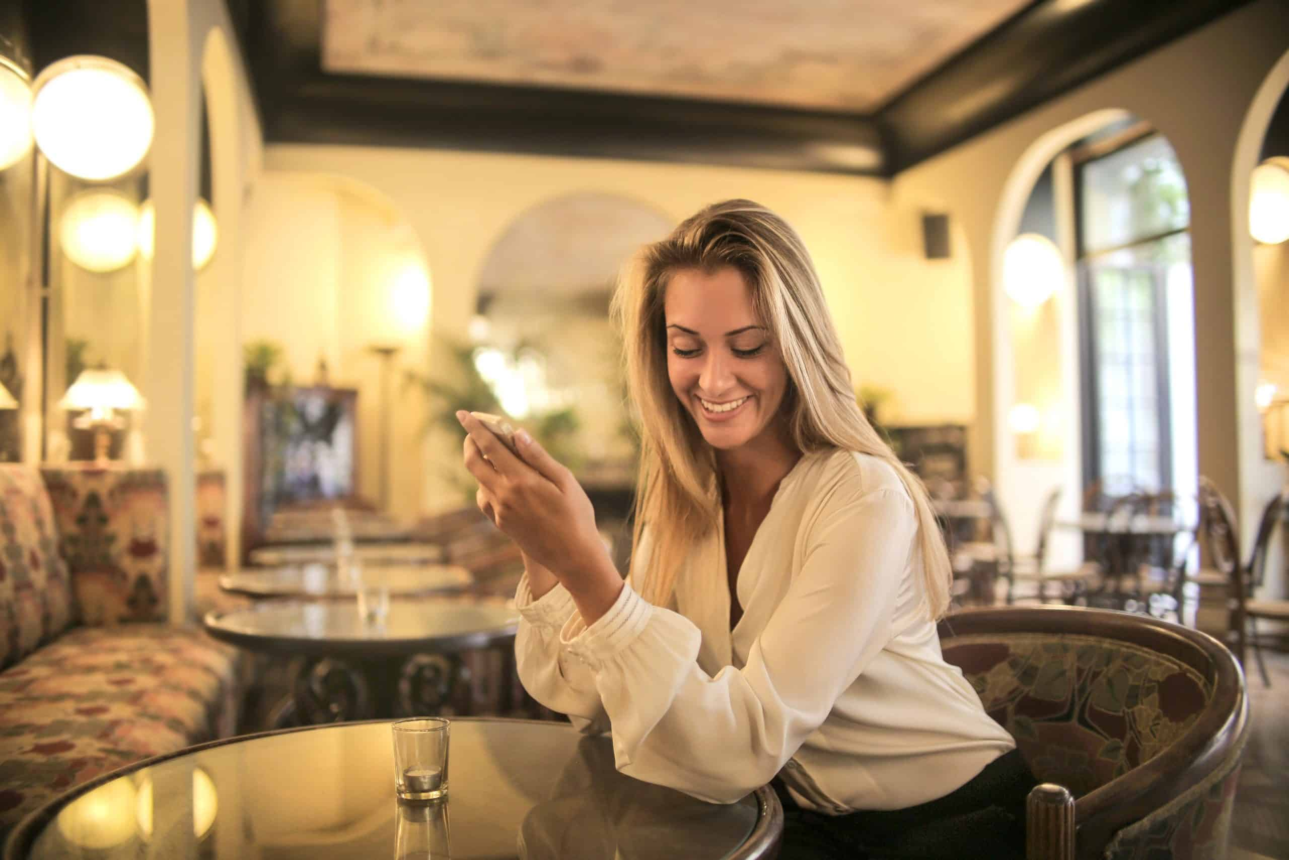 Woman sitting at restaurant with her boyfriend holding her smartphone and smiling
