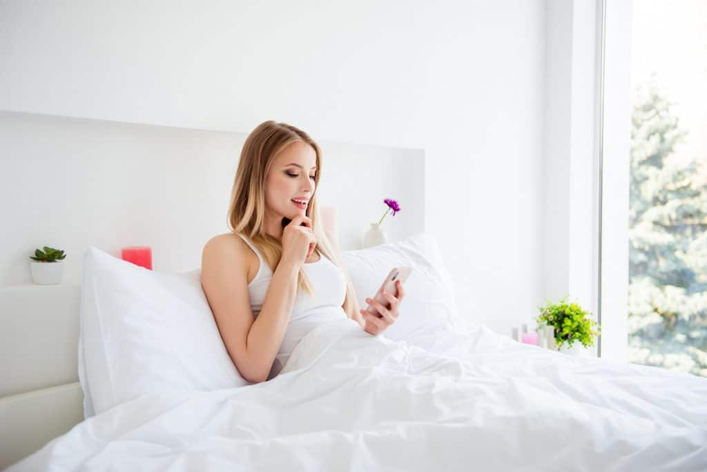 pretty blonde woman bed texting
