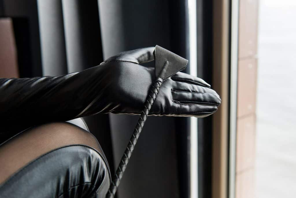 Leather black gloves and lash in woman palms