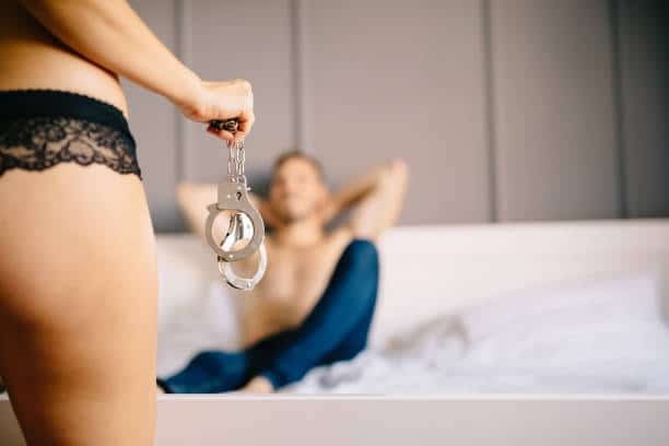 woman in lingerie holding cuffs, shirtless man waiting for her laying on the bed