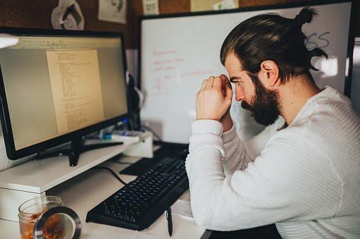 man sitting at his computer looking stressed from work