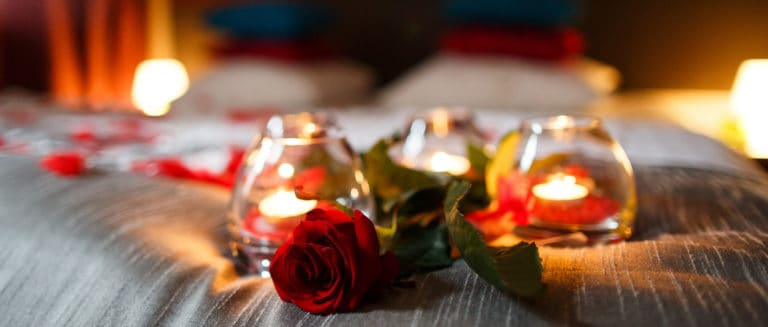 romantic atmosphere - Candles in glass jars and rose petals laid out beautifully on bed