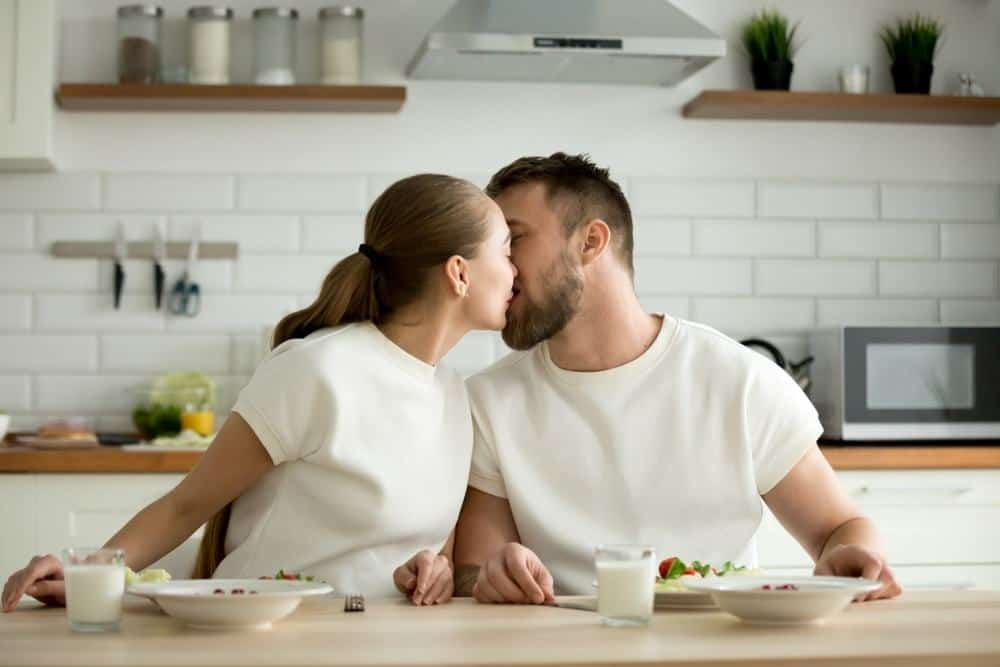 couple kissing in the kitchen