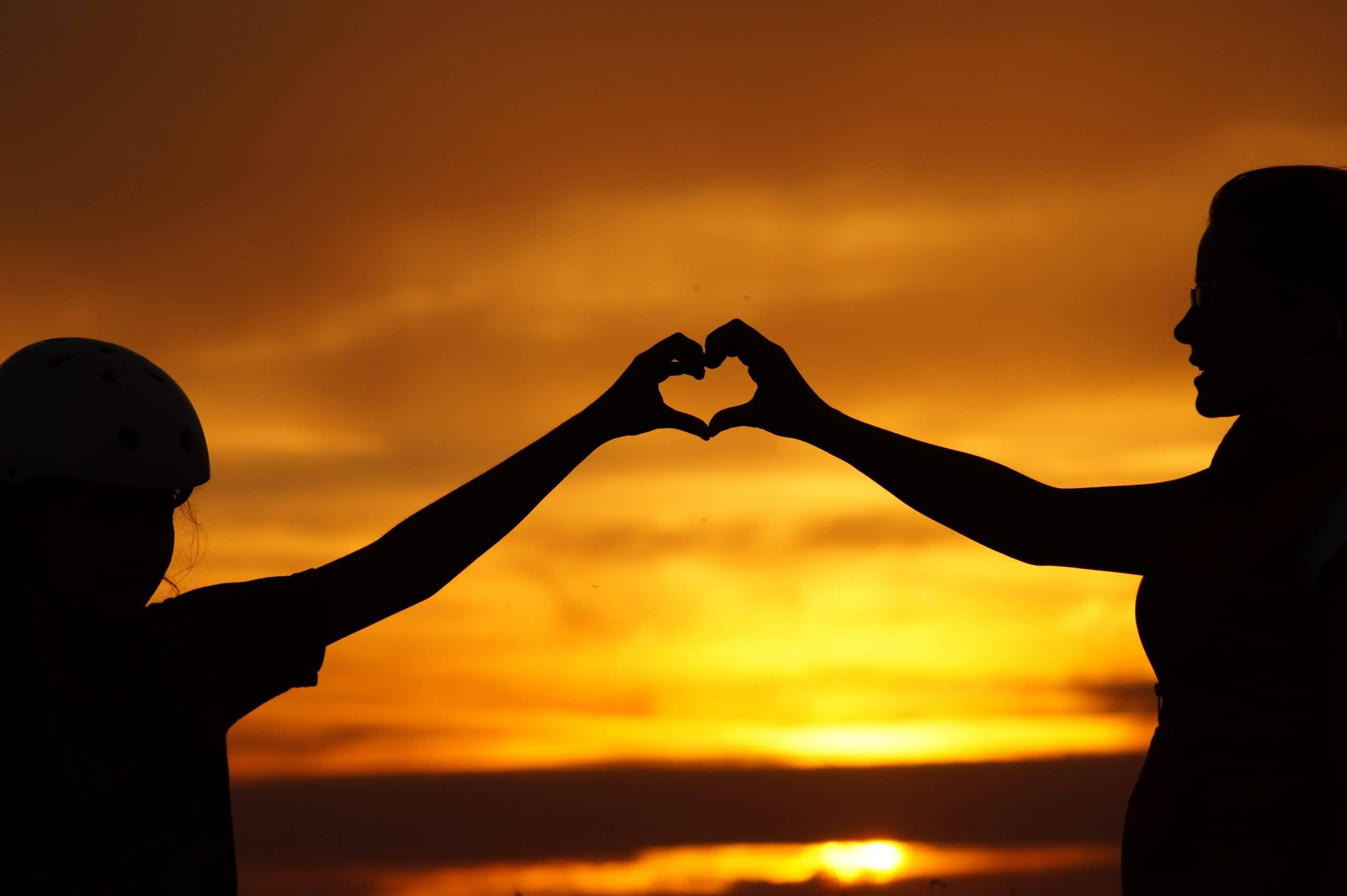 couple on the beach holding arms up and creating joined heart shape at sundown
