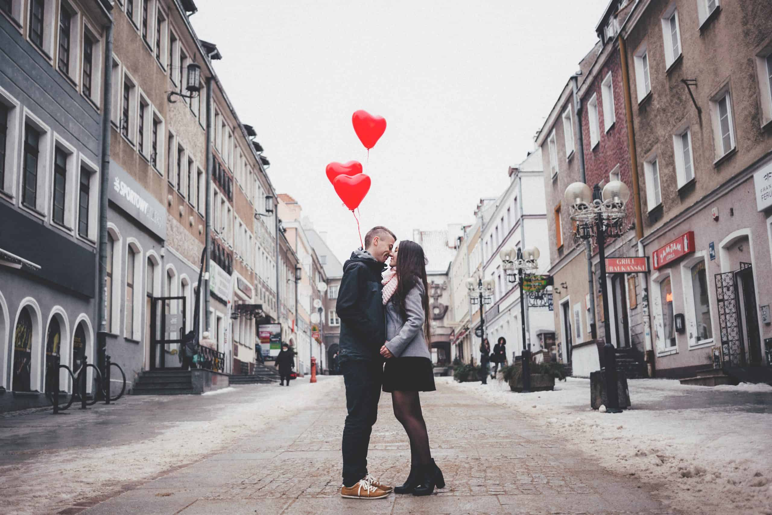 man holding heart shaped baloons kissing his girlfriend in the middle of the street