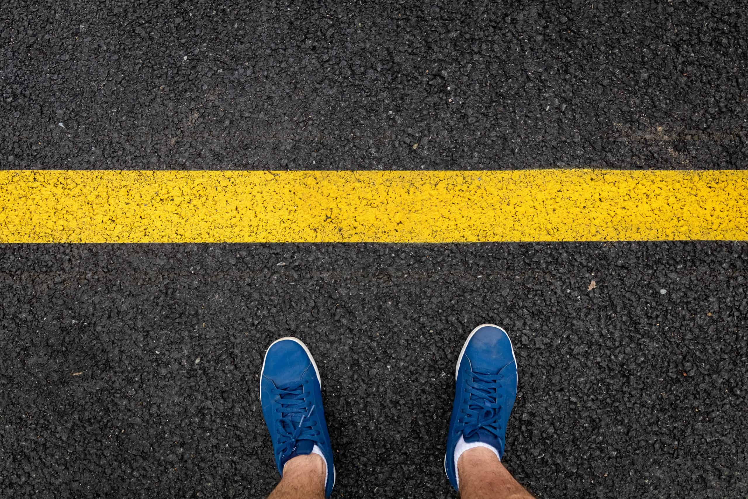 man's feet in front of a yellow line