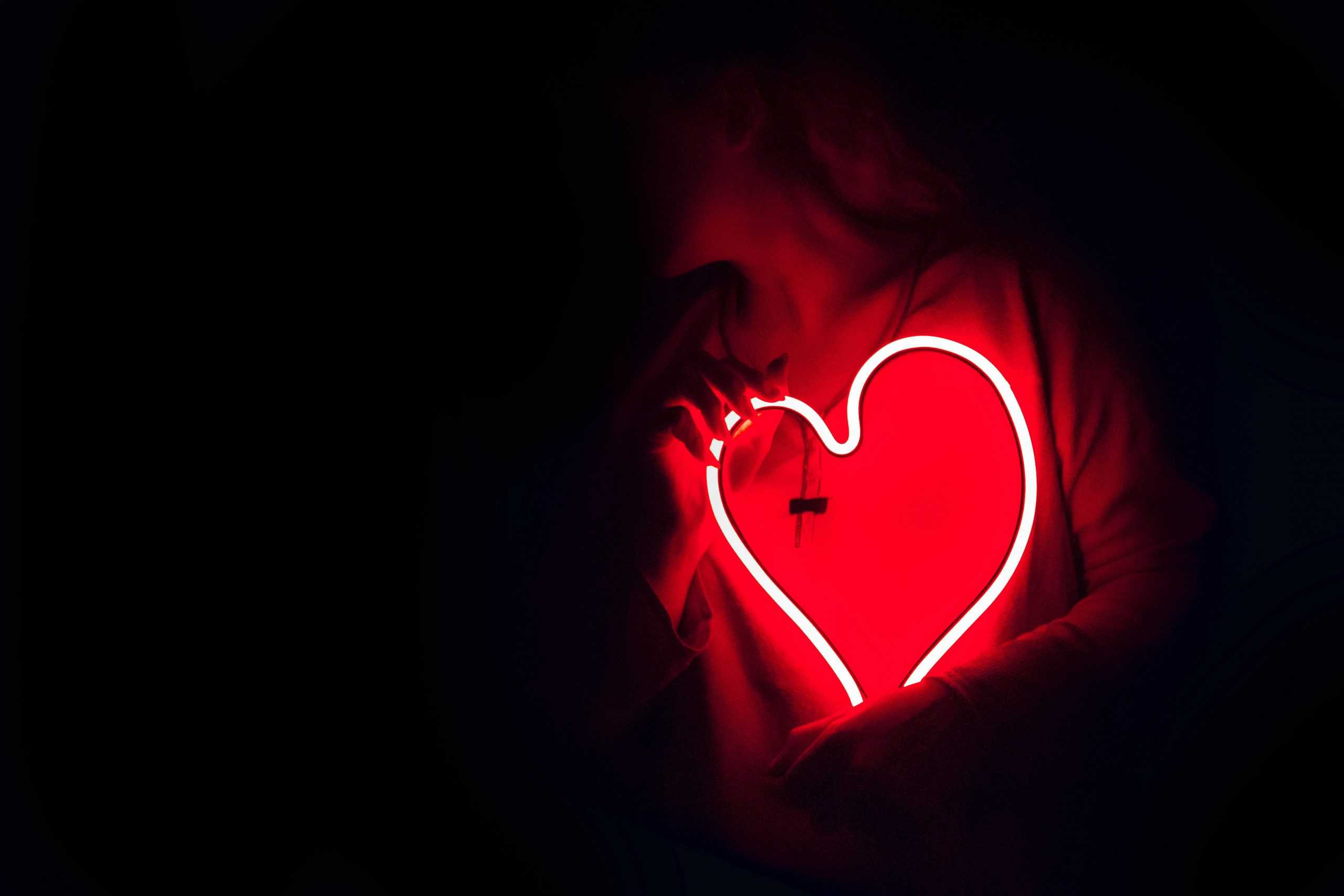 woman holding heart shaped neon sign close to her chest