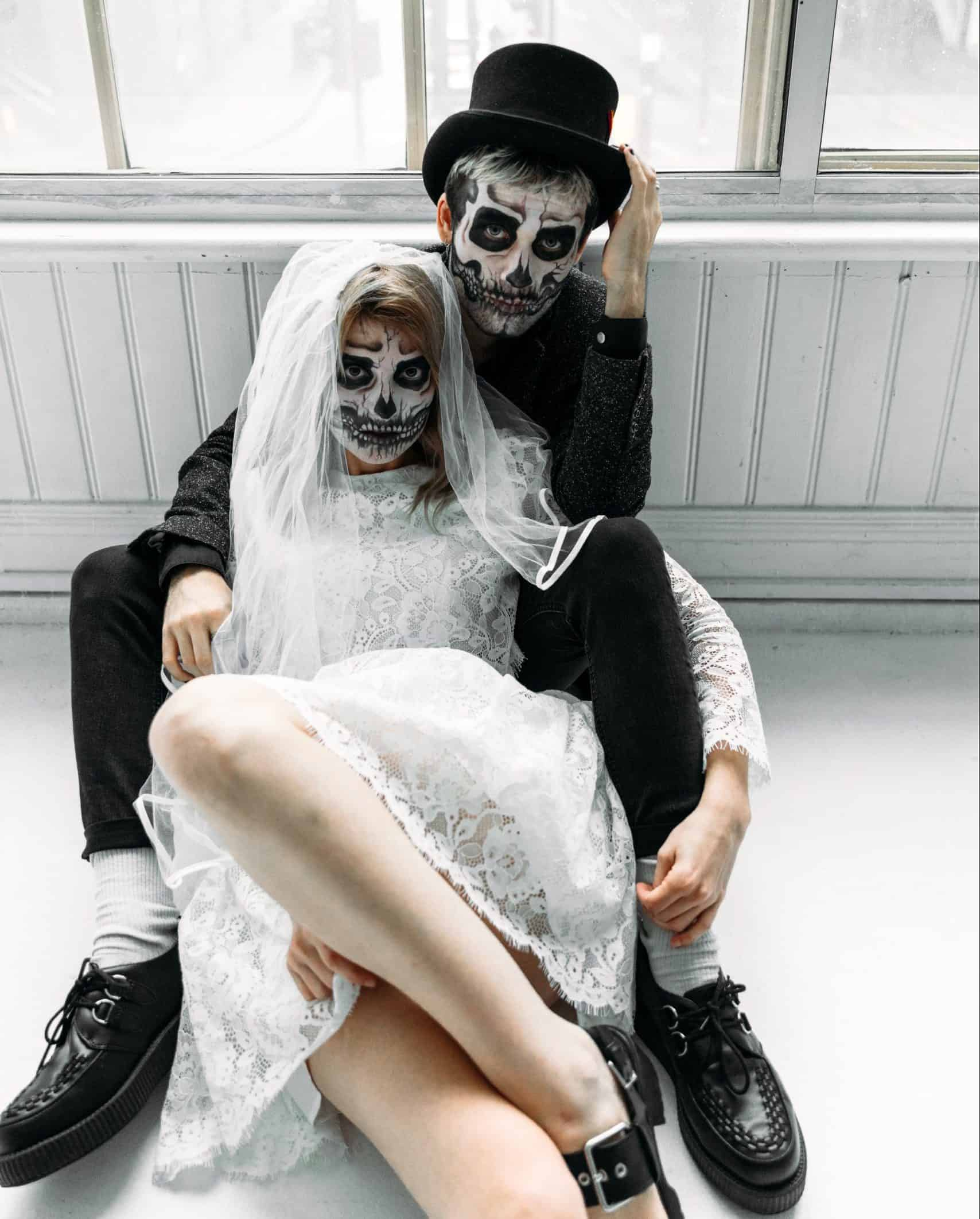couple wearing goth wedding clothes and face skeleton make up