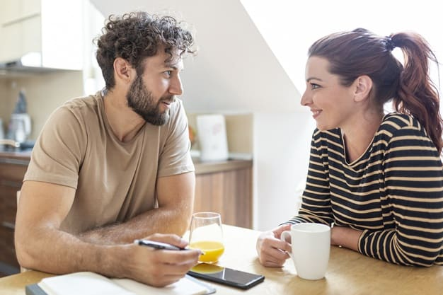 couple having a light but meaningful conversation in the kitchen, looking cheerful