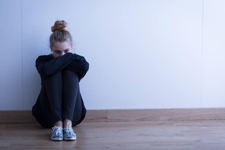 sad woman sitting alone on the floor