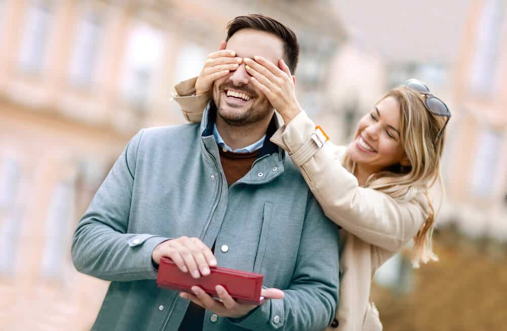 woman giving her husband a birthday gift