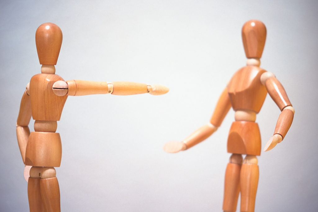 wooden figures, male and female,  one pointing at the other