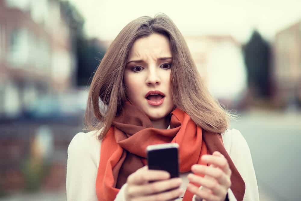 woman shocked looking at the phone