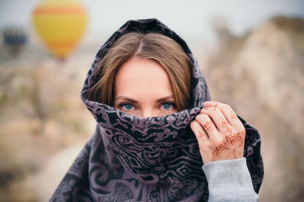 A woman looking at the camera with a scarf covering her face