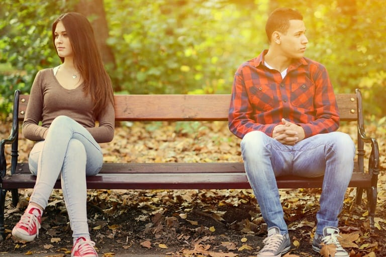couple on a bench ignoring each other