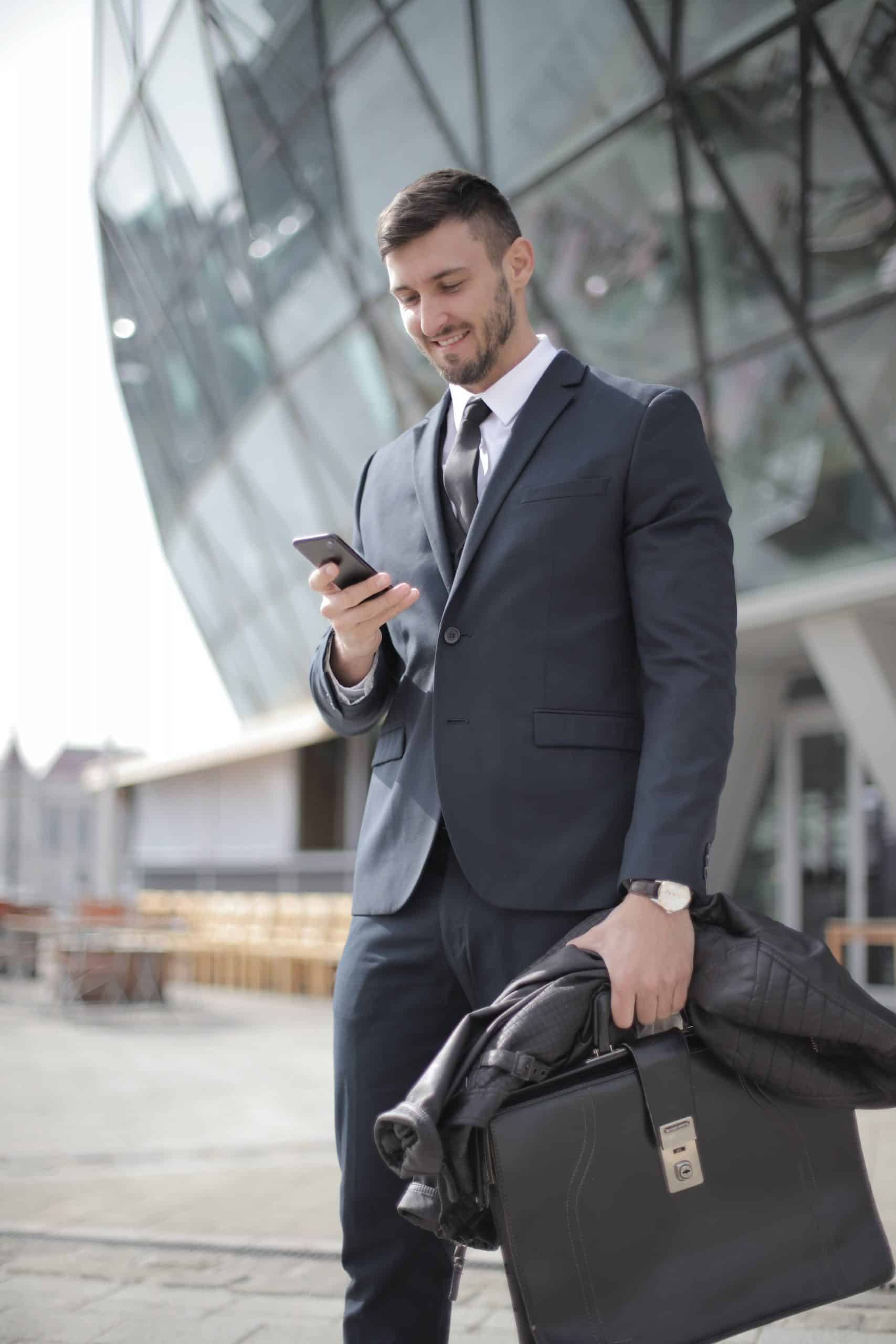 man in suit holding briefcase and looking at his smartphone smiling