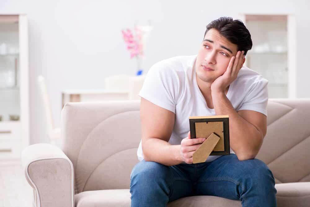 man holding photo thinking