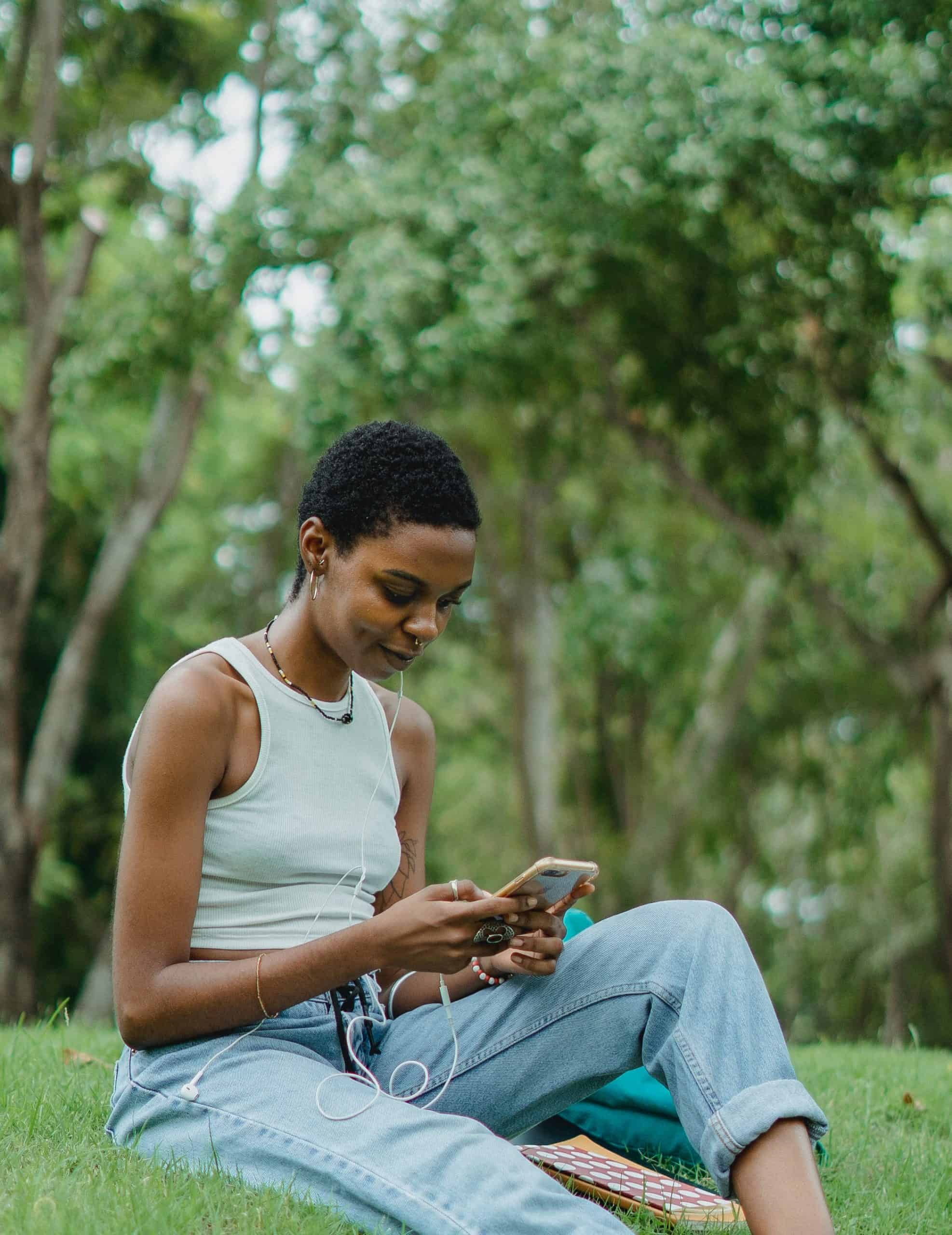 smiling african american woman sitting on the grass using her smartphone