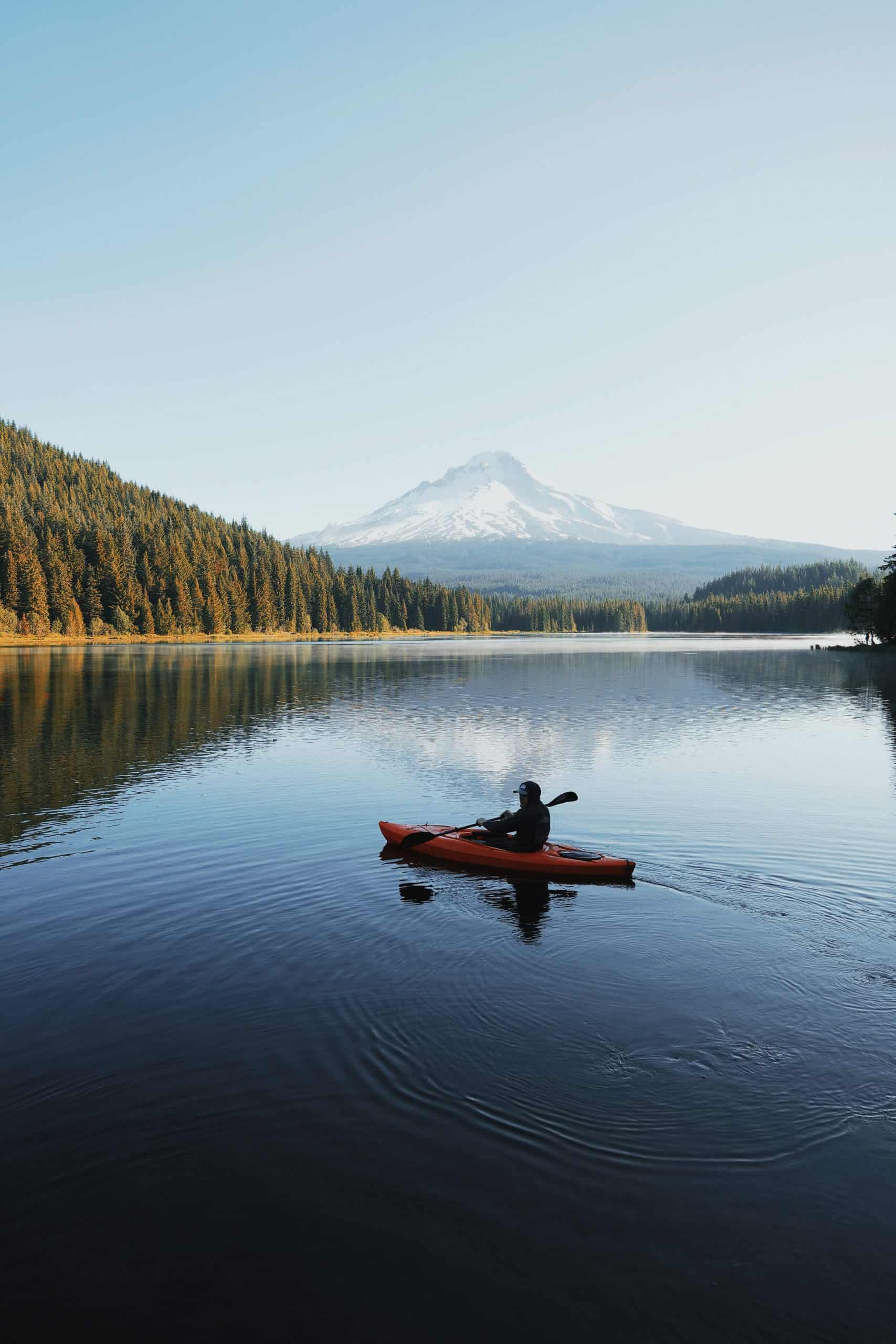 person riding kayak on river in front of mountains and forest in the background