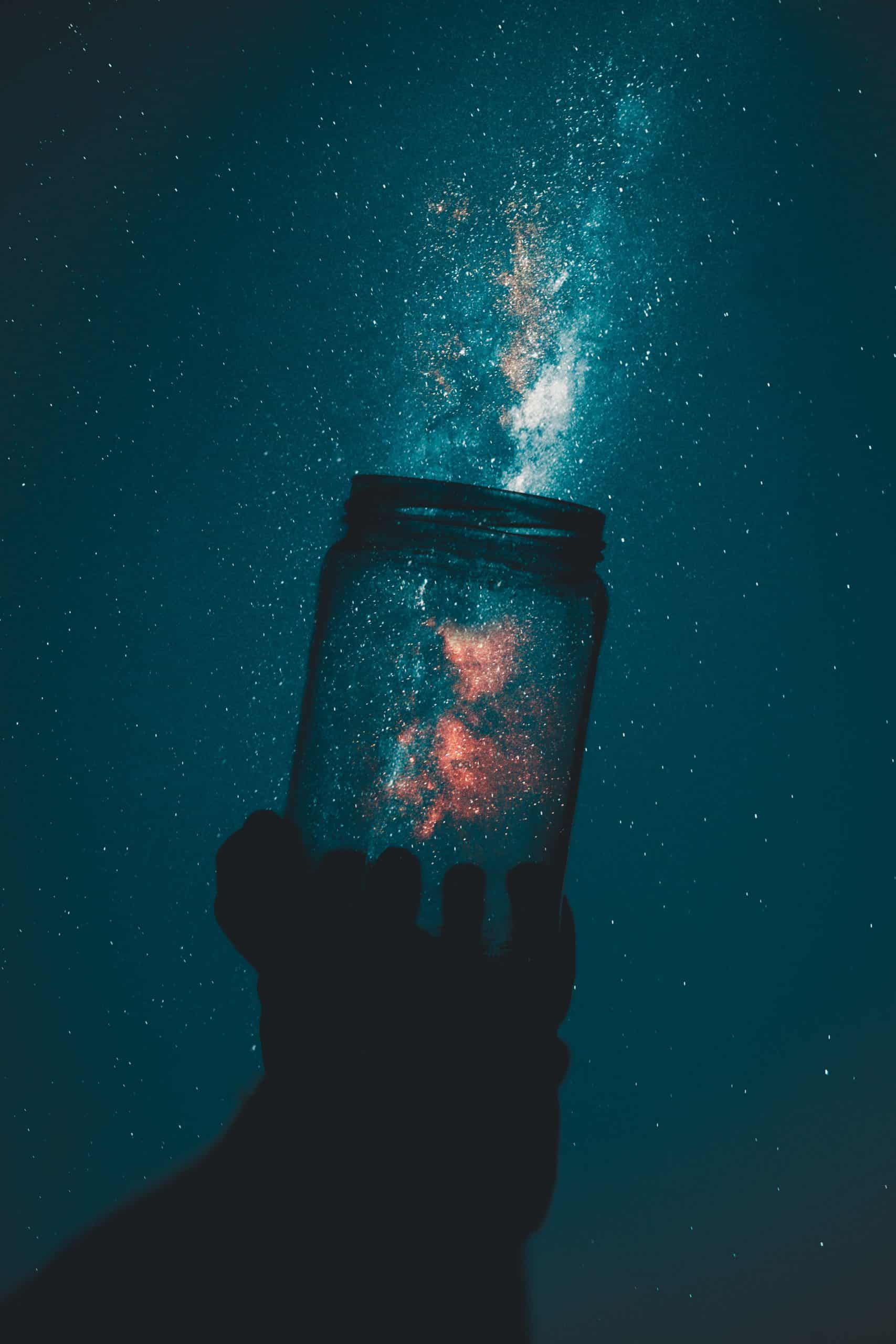 silhouette of hand holding a glass jar pointed at night sky, capturing stars