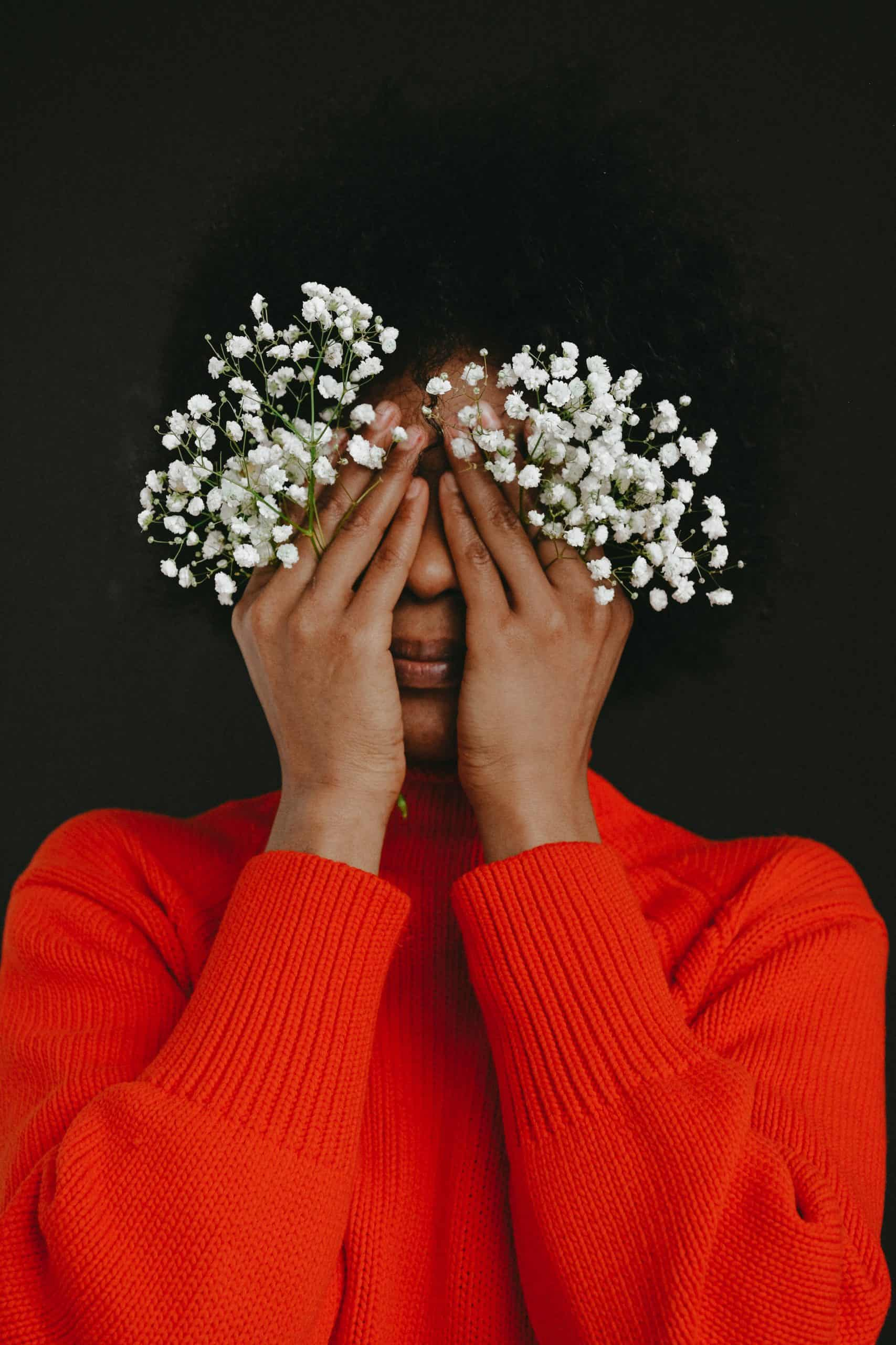 woman holding white flowers covering her face with her hands