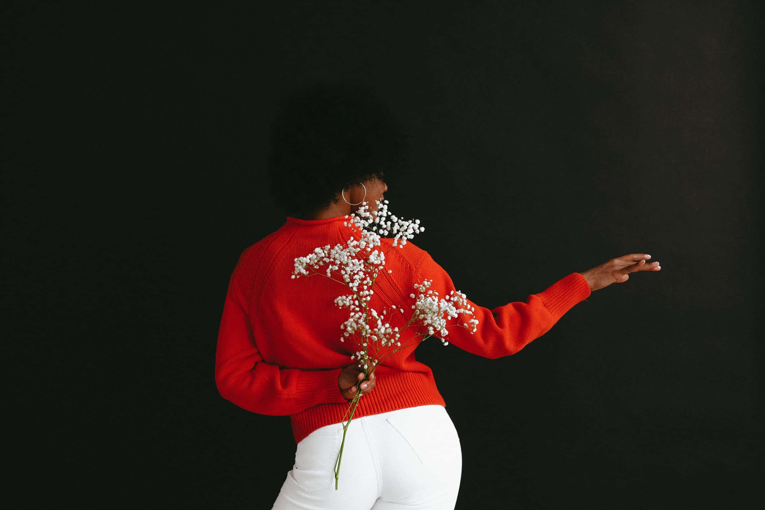 woman with back turned wearing red sweater, holding flowers behind her back and gesturing away with the other hand