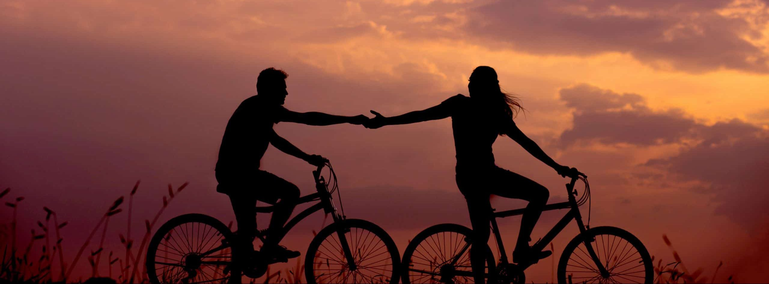 Woman holding man's hand on bicycle