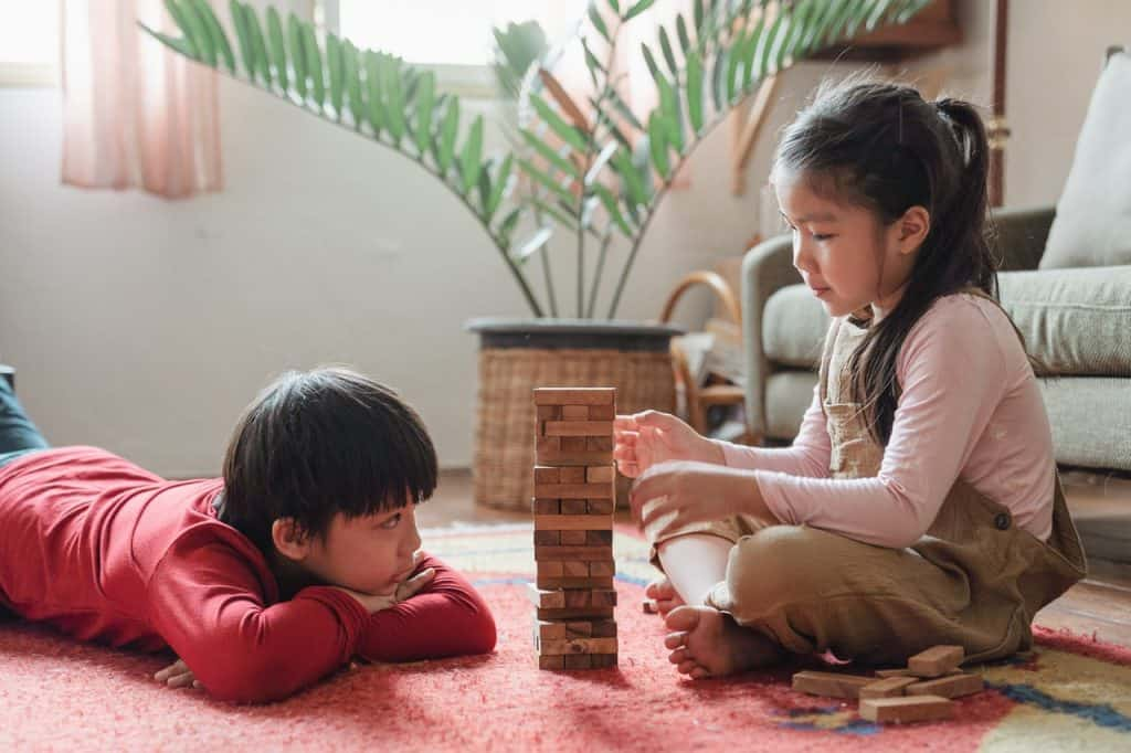 Boy and Girl sitting and playing with building blocks
