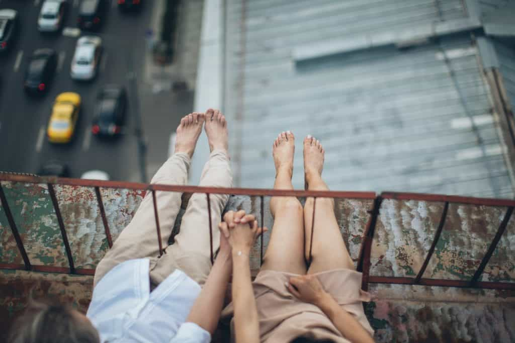 Barefoot man and woman sitting on bridge holding hands with their legs hanging out over a freeway