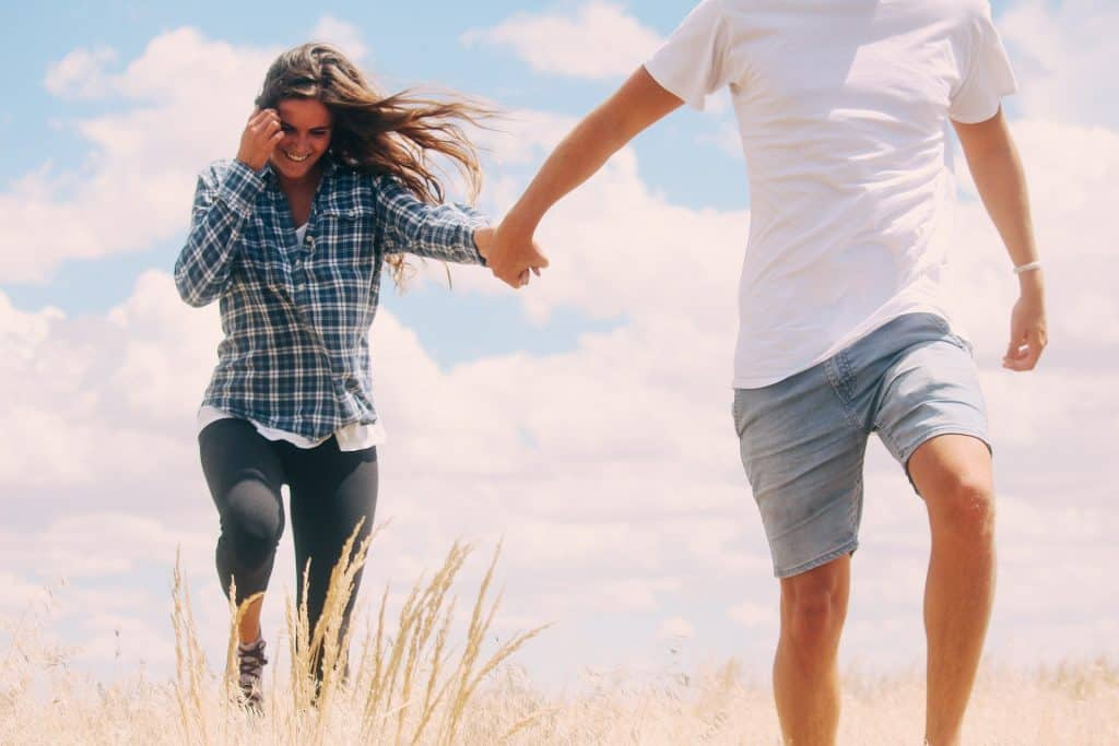 Couple holding hands in a field, girl is walking slightly behind, touching her her and smiling