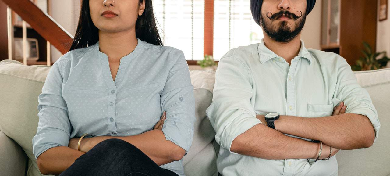 Male and female couple sitting next together and crossing arms in dissatisfaction