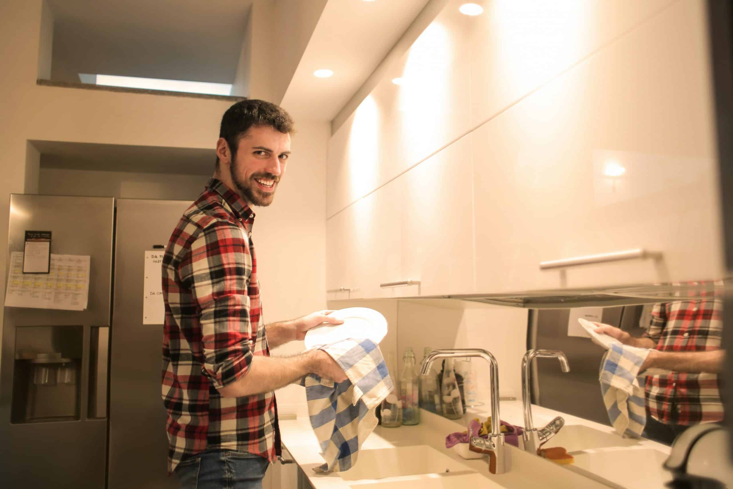 woman taking a picture of her cheerful boyfriend washing the dishes