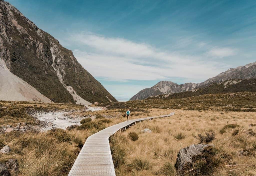 Woman walking down a single beautiful valley trail on mountain landscape
