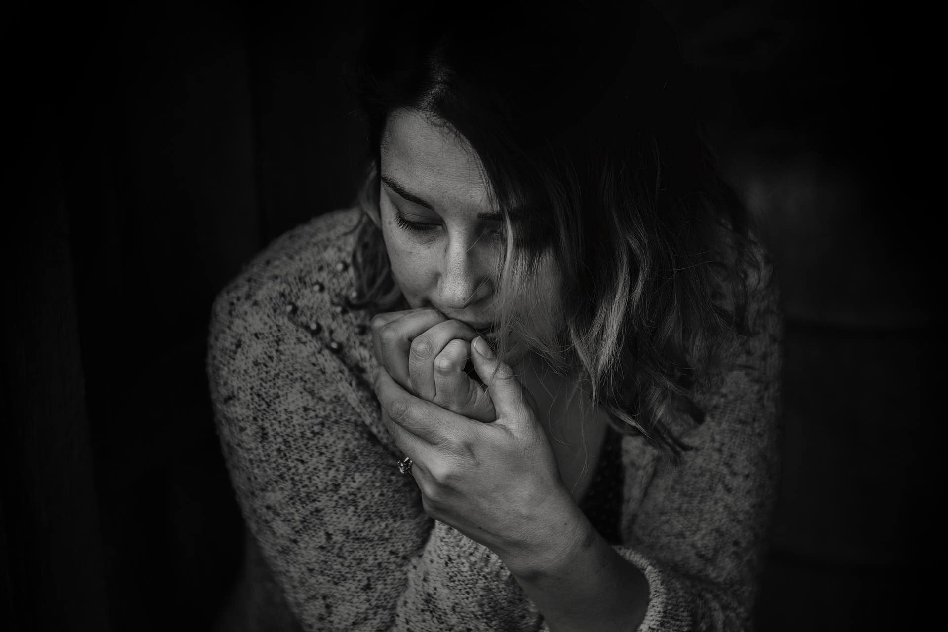 anxious woman sitting and biting her fingernails