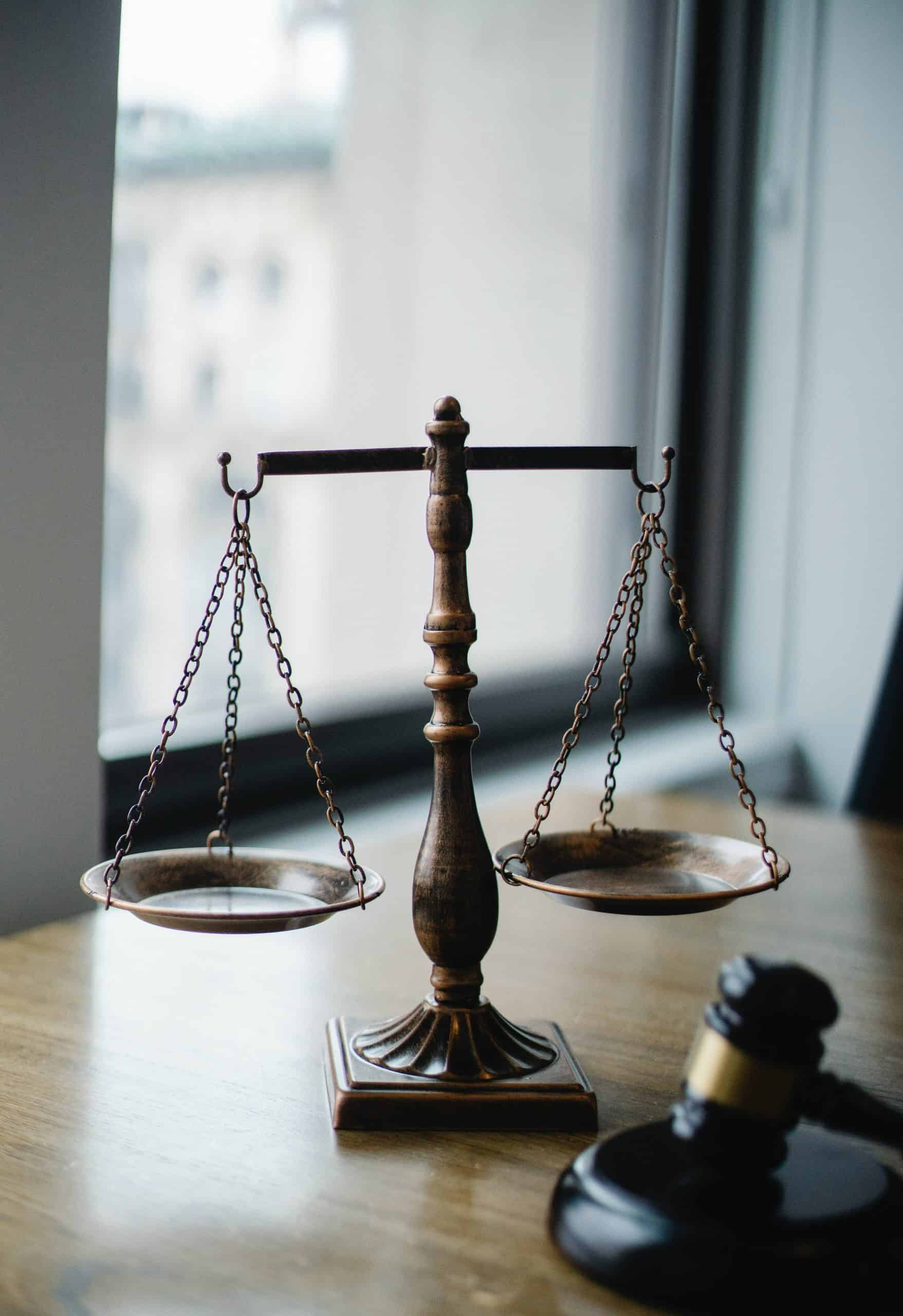A judge's scale and gavel resting on a table