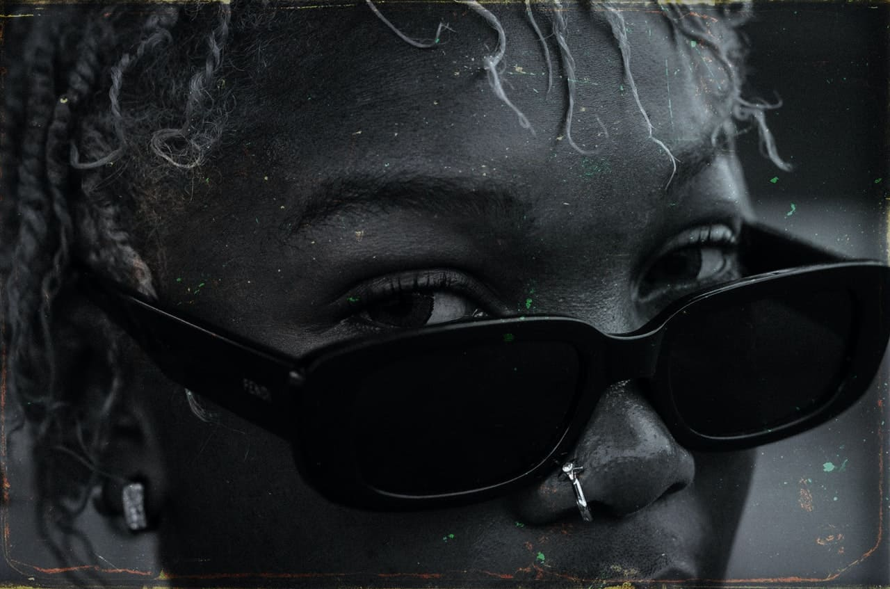 woman wearing sunglasses with eyes peaking above with a powerful stare