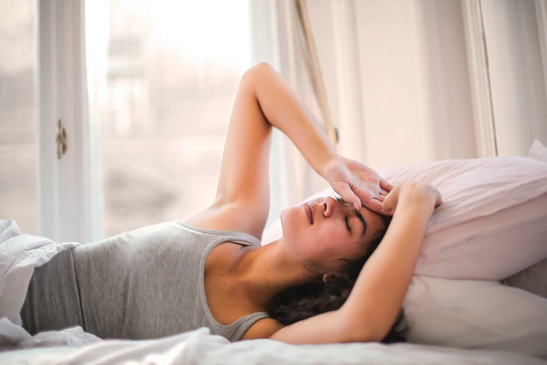 exhausted woman lying on her bad and holding her head with both hands