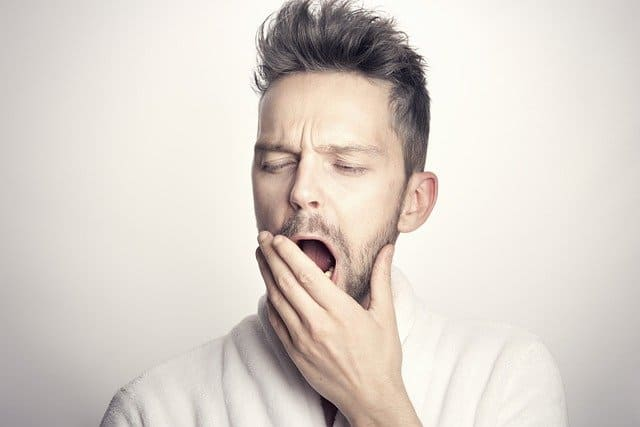 guy yawning with his hand covering his mouth
