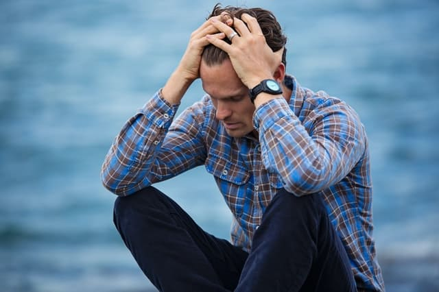 stressed guy sitting by the ocean holding his head with both his hands and pulling his hair back