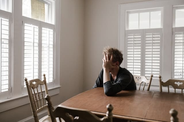 guy in dining room looking stressed and holding is head