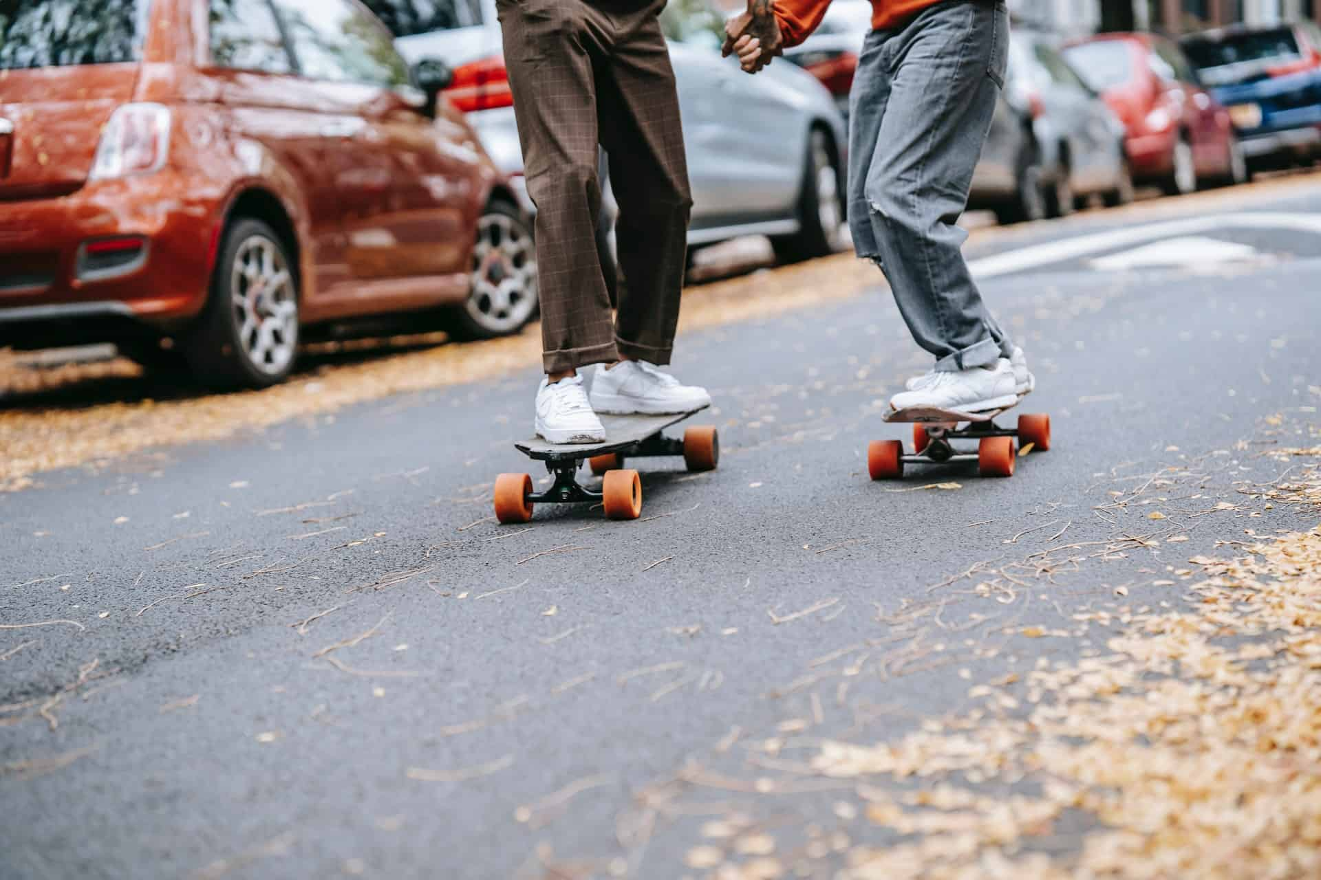 man and woman skateboarding and holding hands