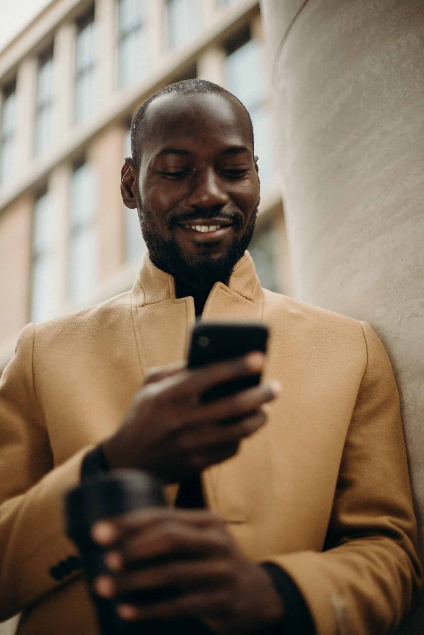 man looking at his phone smiling and reading a text message