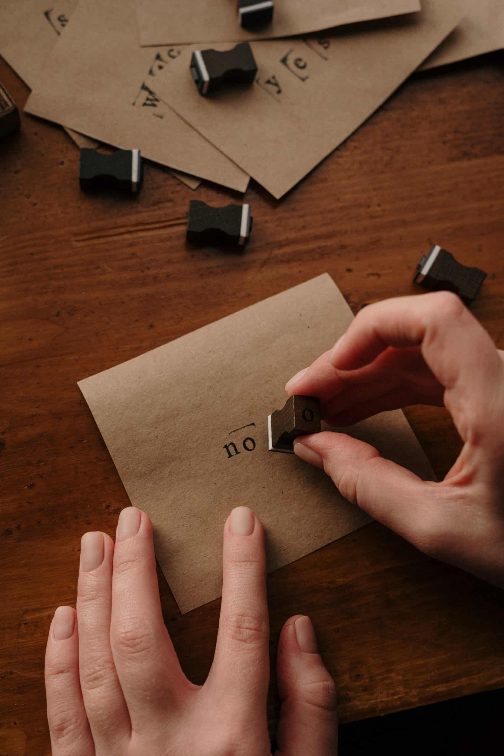 person holding piece of paper stamping the word 'no' on it
